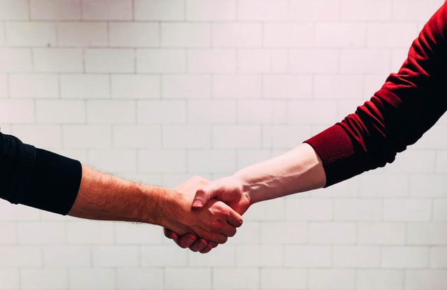 Conflict Resolution Skills two people shaking hands